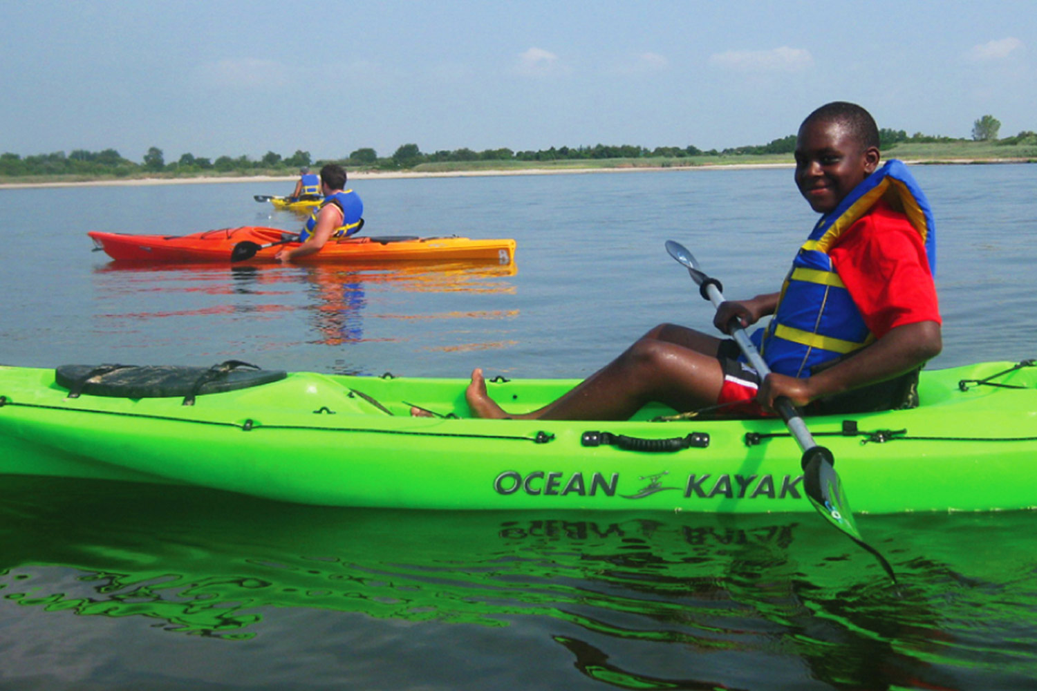 A child sitting in a bright green kayak on the Jamaica Bay estuary, with two other men in kayaks on the water behind him