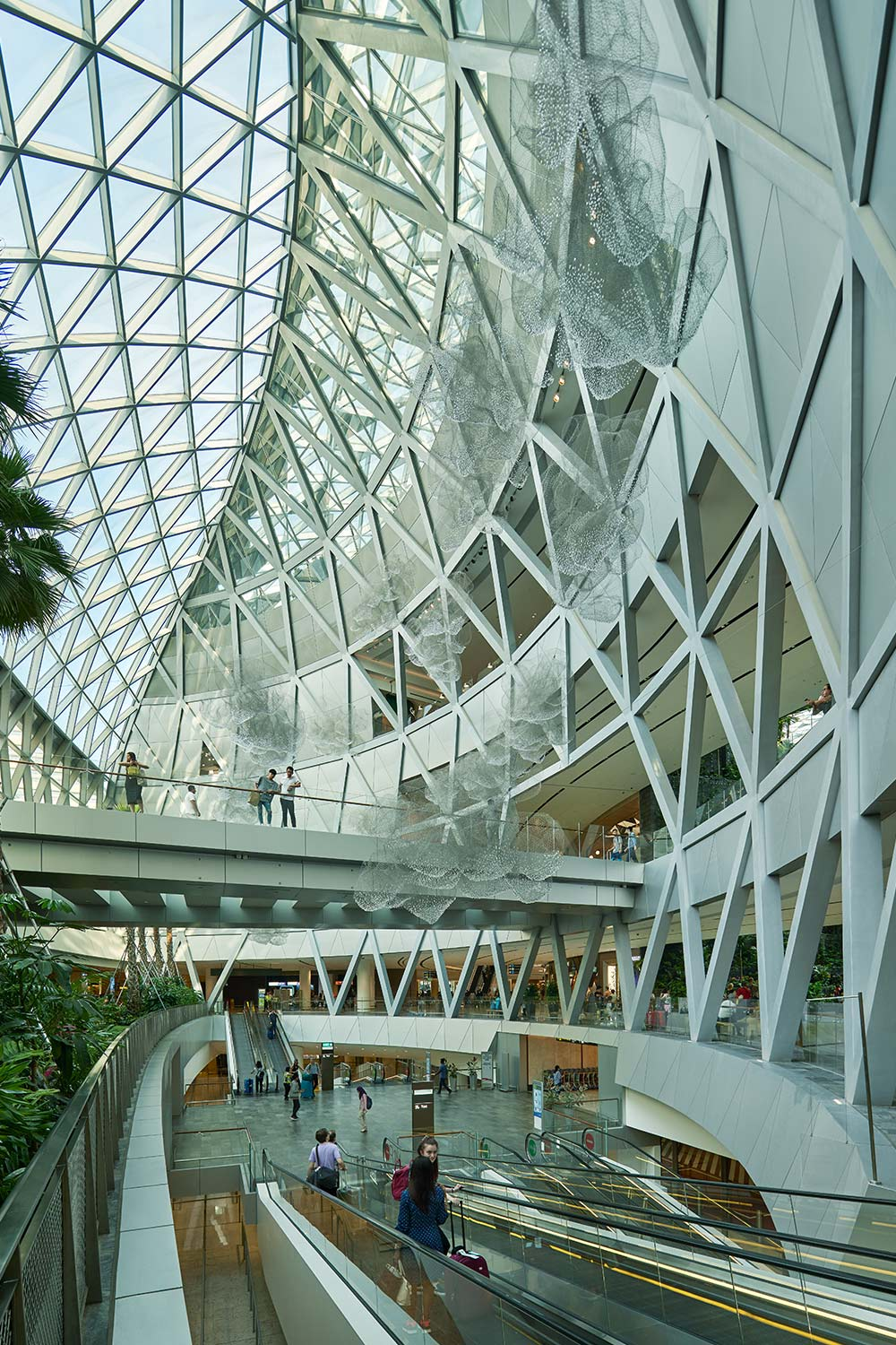 International travellers walking through the structurally unique Jewel Changi Airport
