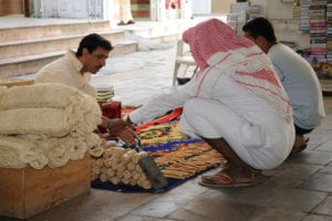 Two Saudi Arabian people in the Makkah Region speaking with the owner of a street market stall