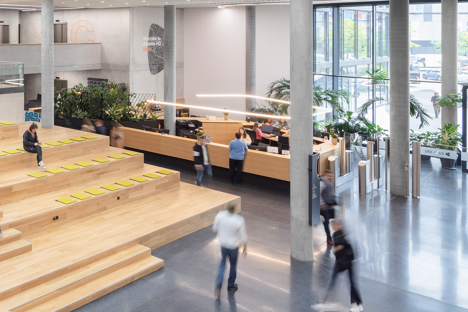 Busy Zalando employees walking through the spacious foyer of the new headquarters