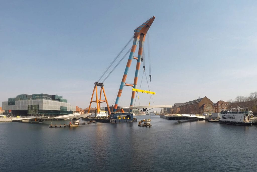 Lille Langebro bridge in construction: large blue and orange ship lifts section of the bridge into place on the river