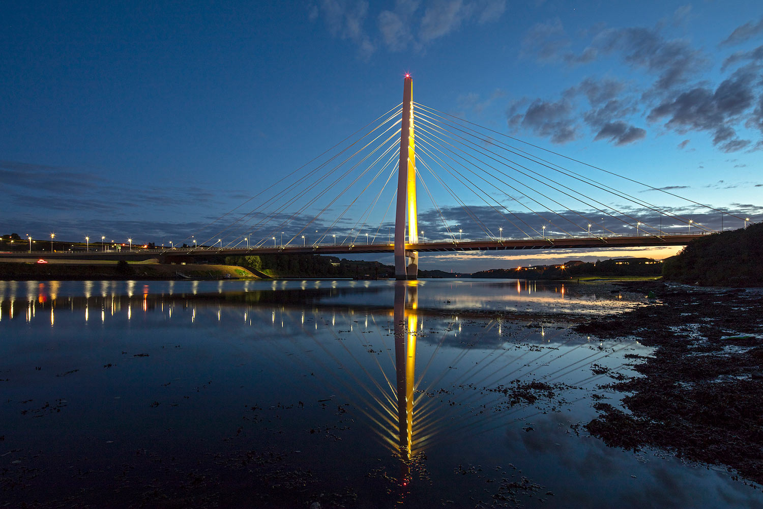 Northern Spire glows yellow between a moody river and grey sky