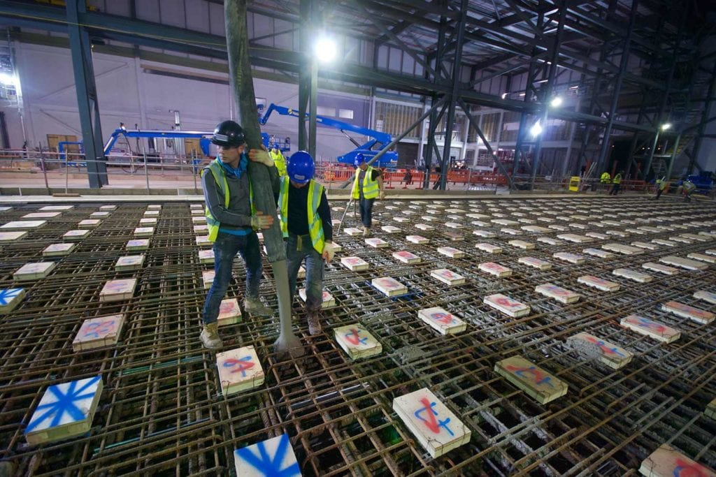 Two construction workers pour concrete into the floor of the Airbus extension at night