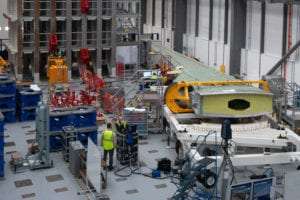 Interior view of Airbus Wing Integration Centre, with workers in high-vis jackets dotted around the space