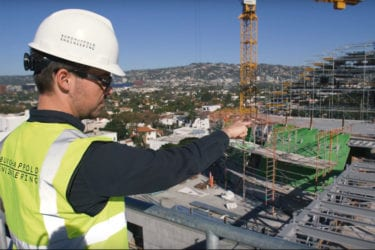 A BuroHappold employee in high-vis work gear points on a construction site