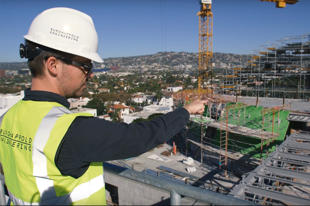 A Buro Happold employee in high-vis work gear points on a construction site