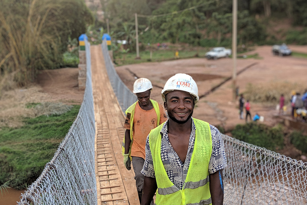 Two happy locals with high-vis jackets on, walking across bridge towards the camera