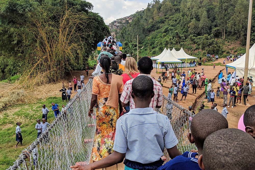 Large group of people crossing Gatare Bridge with many onlookers gathered below