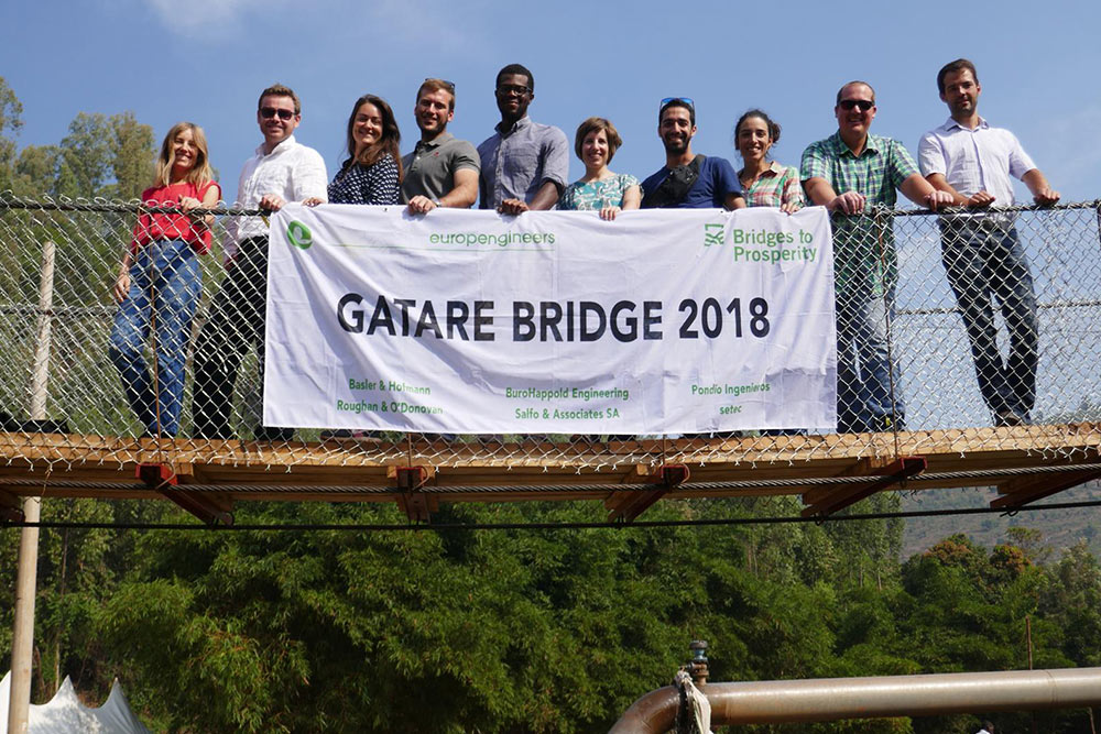 Team of people on small bridge holding a banner which reads 'Gatare Bridge 2018' and lists those involved.