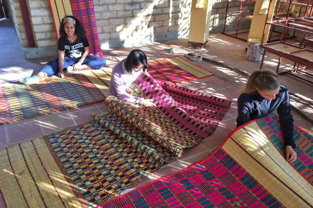 Students and engineers creating rugs for the Agri-Tech school