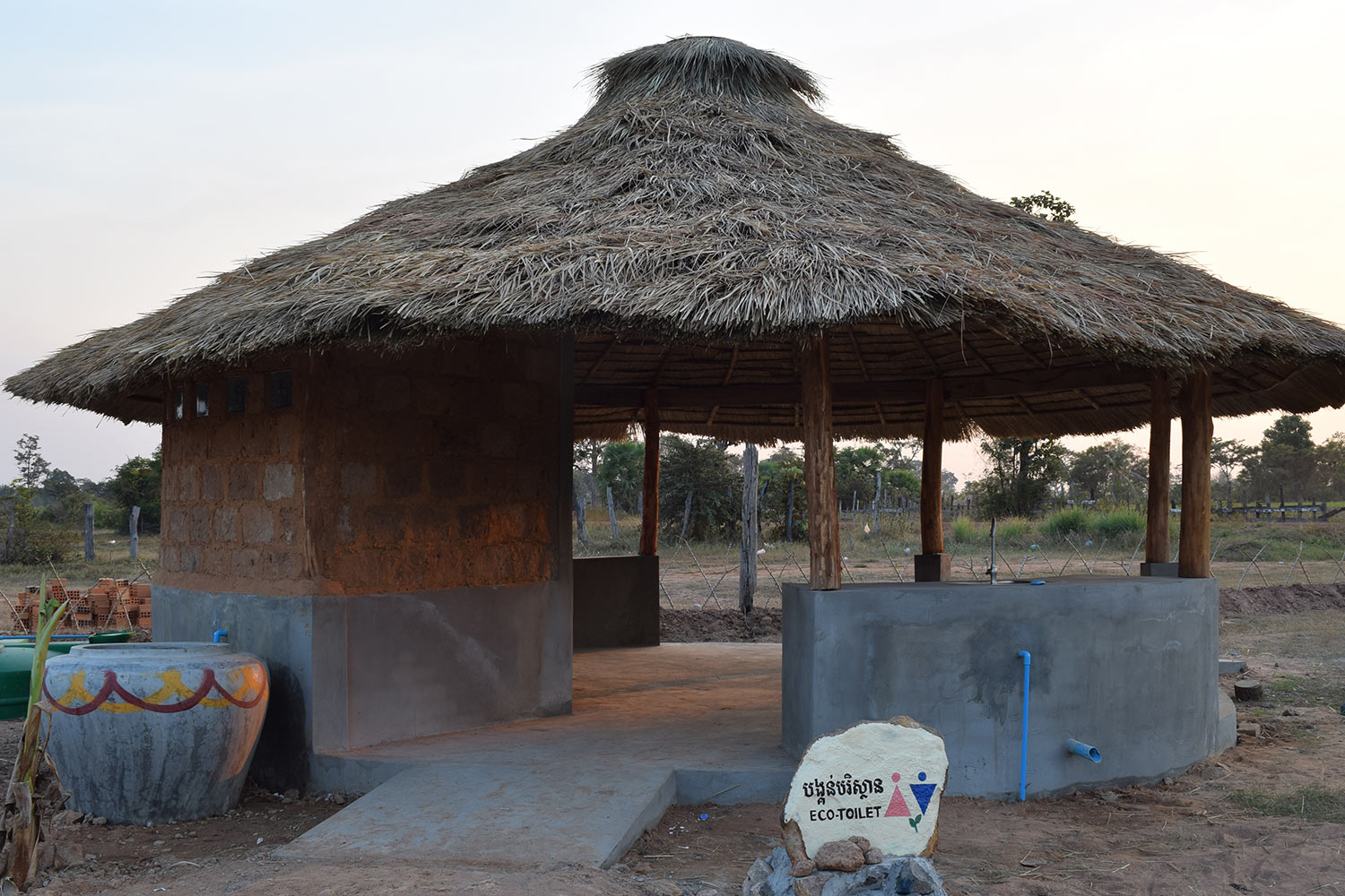 Eco-toilets situated within a small, straw-roofed hut