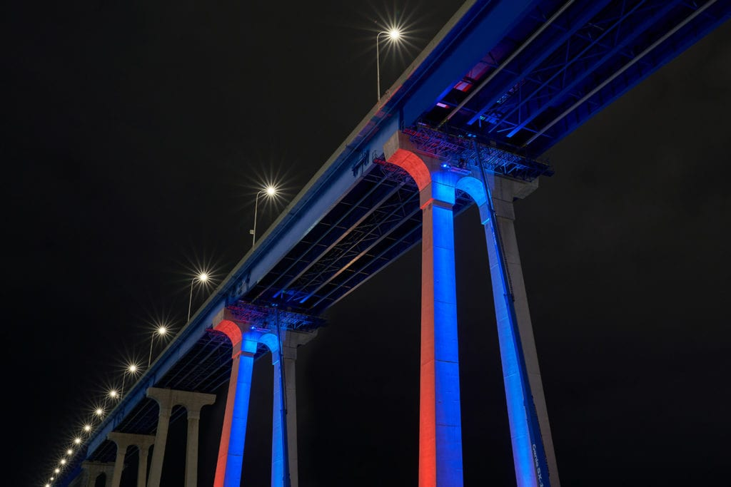 Coronado Bridge lit up at night in orange and blue