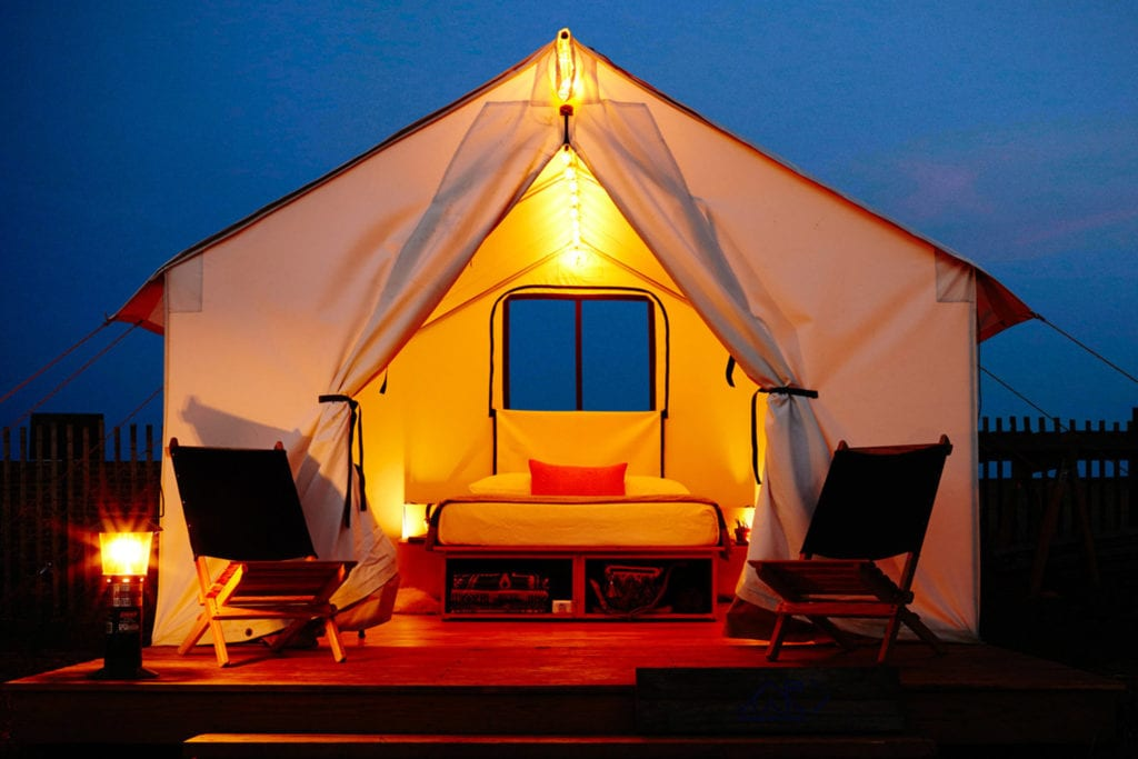 Glamping tent at Fort Tilden, lit up yellow against the dark evening sky