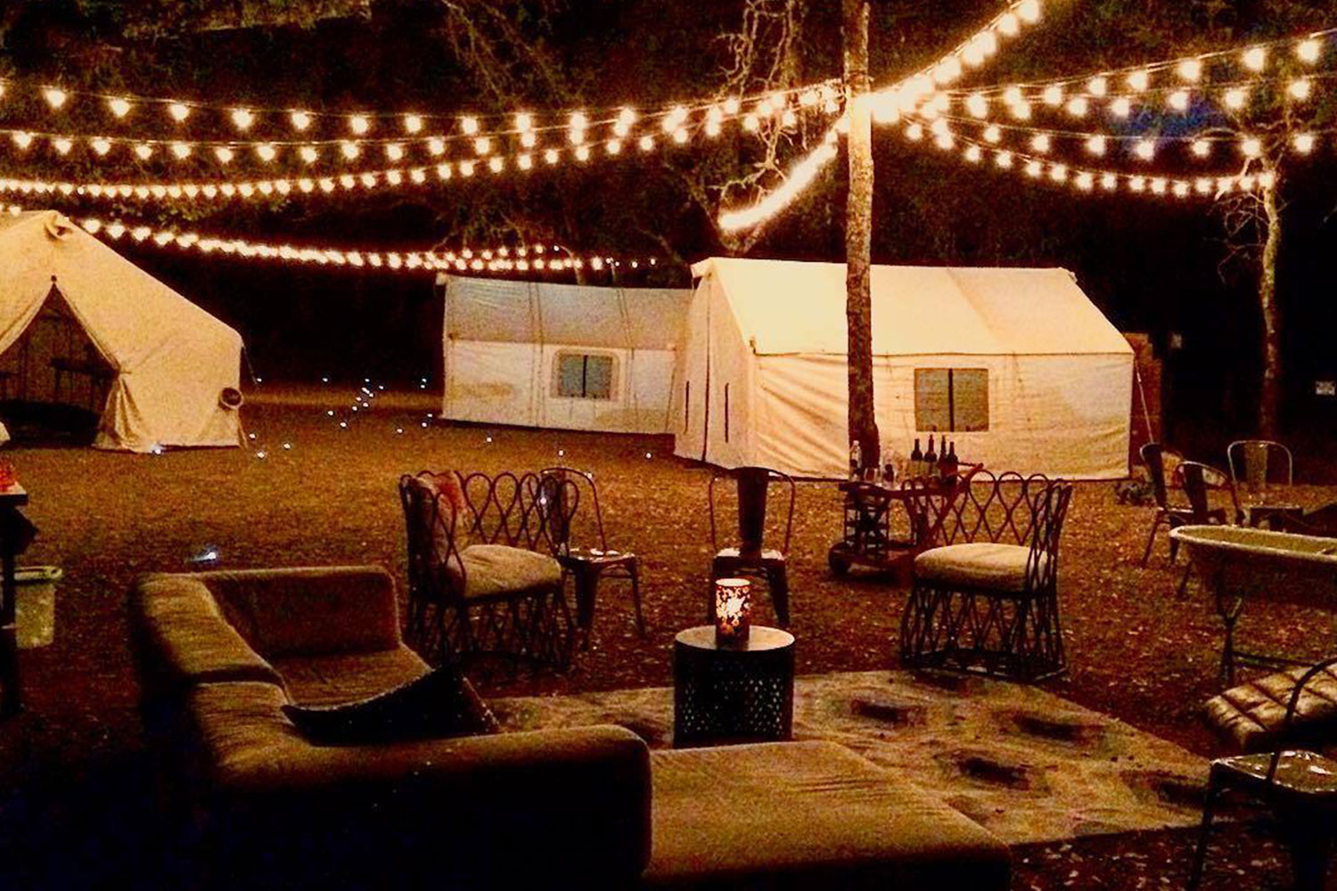 Cozy seating area at Fort Tilden by night, lit by string lights between trees above