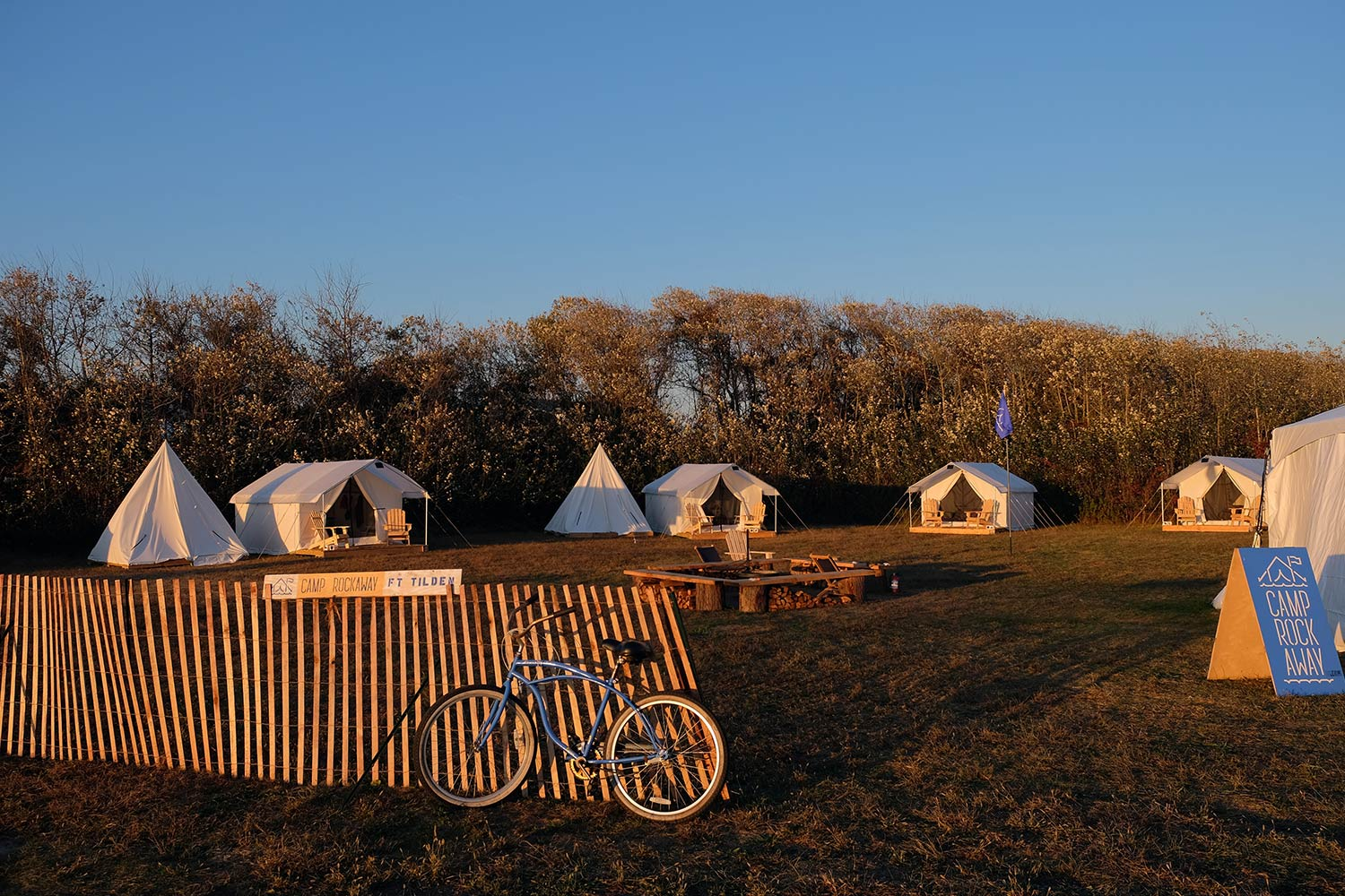 Sun setting over Camp Rockaway at Fort Tilden, where a blue bike rests in the foreground against a fence