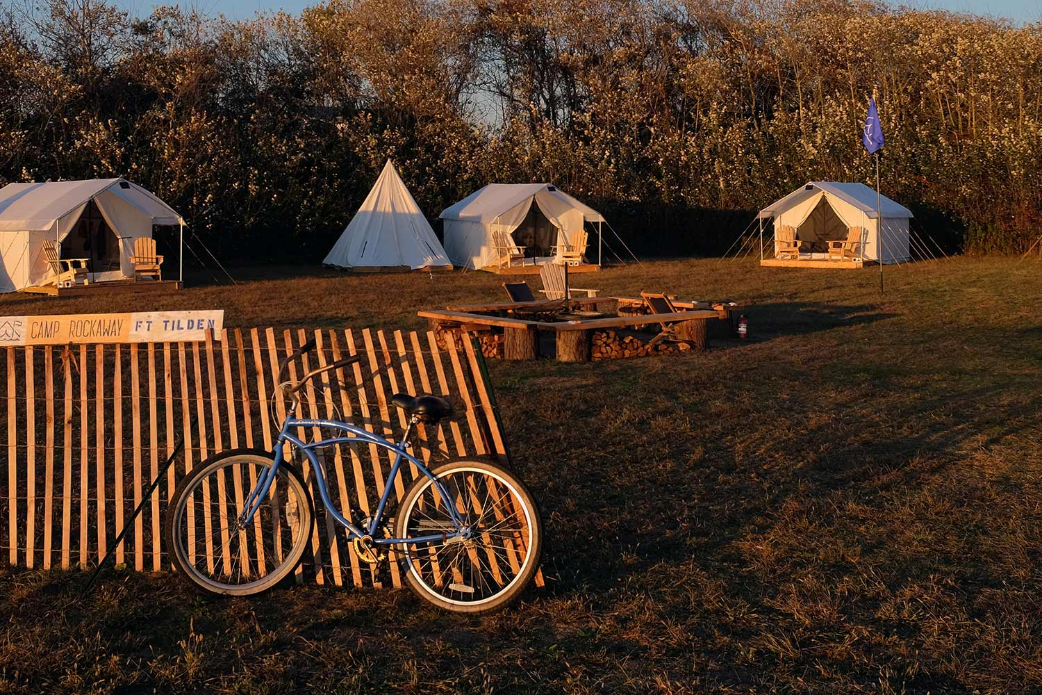 Sun setting over campsite at Fort Tilden, where a blue bike rests in the foreground against a fence