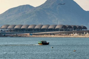 Hong Kong Passenger Clearance building shot from across the water, where a boat crosses in the foreground