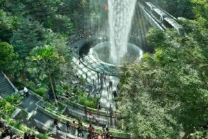 An aerial view of international travellers gathering around the indoor waterfall, almost hidden amongst the greenery at Jewel Changi Airport