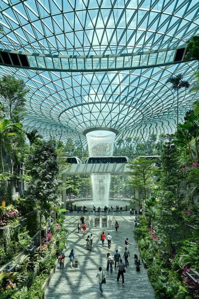 People walking through a nature-themed environment, towards Jewel Changi Airport's astonishing 40m-tall indoor waterfall
