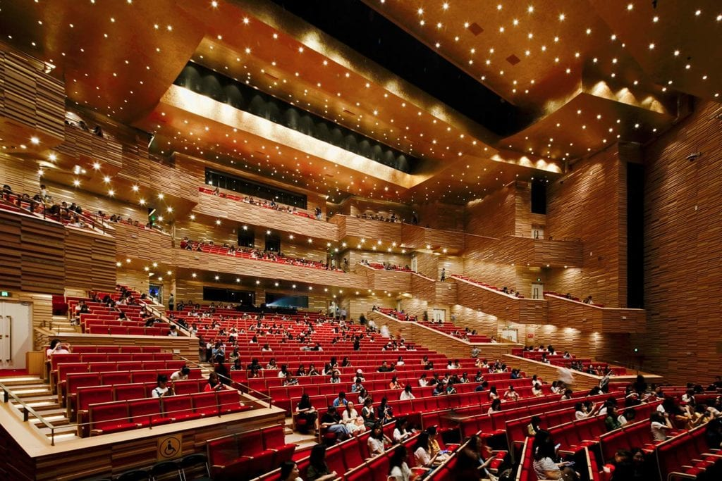 People gathering inside the Yuhang Cultural Arts Centre theatre, between red seating and golden walls and ceiling