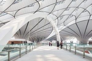 Interior view of people walking through Beijing Airport