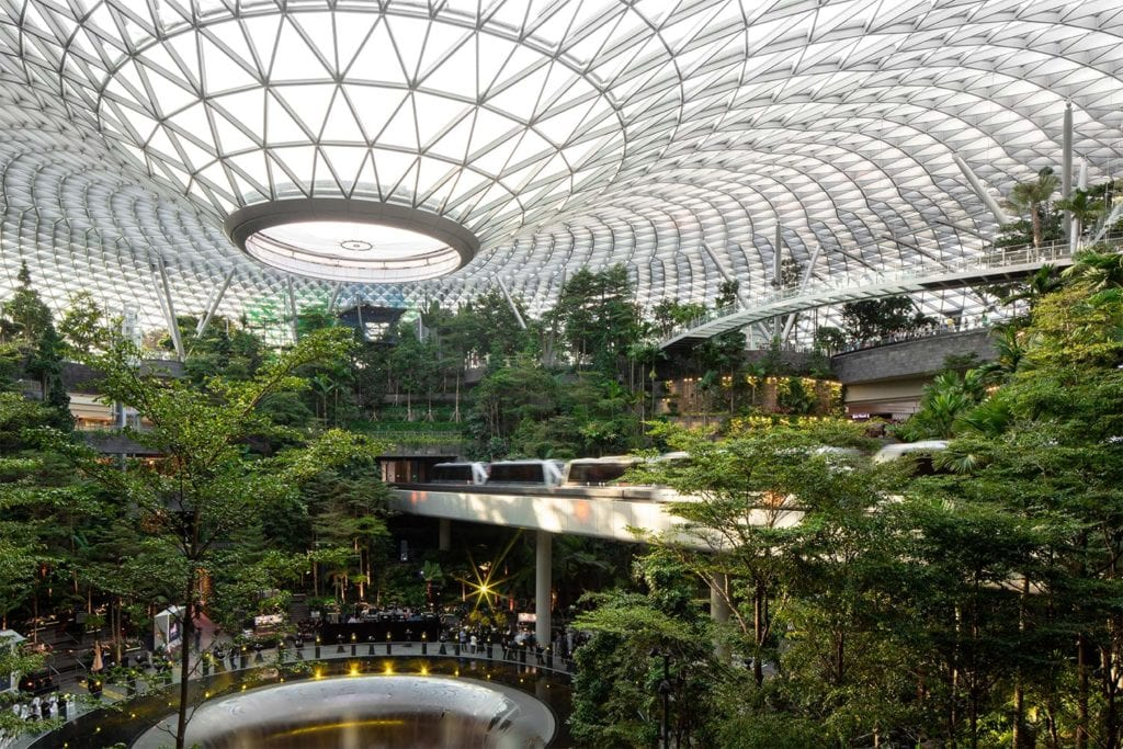 A train carries passengers through Jewel Changi Airport's canopy of trees