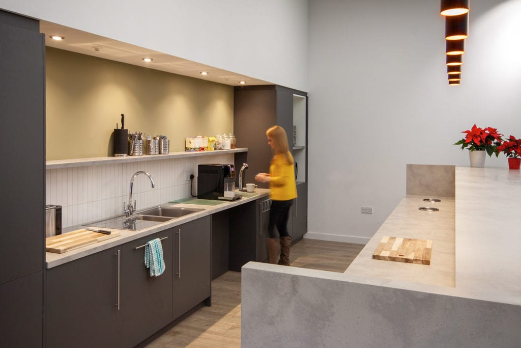 Photograph of woman using the open plan kitchen at Buro Happold's new Leeds office