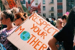 sign with earth at climate week march